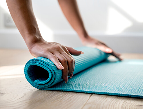 Women's hands on yoga mat