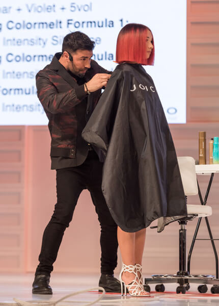 Richard Mannah on-stage at event cutting models hair