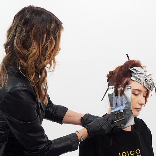 Hairstylist Larisa Love coloring clients hair